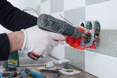 Renovation and construction in kitchen, close-up of electricians hand installing outlet on wall with ceramic tiles using. Professional tools royalty free stock image