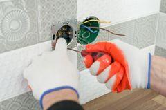 Renovation and construction in kitchen, close-up of electricians hand installing outlet on wall with ceramic tiles using. Professional tools stock photo