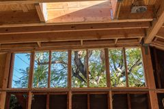 Renovation construction showing added stud wall to raise roof height, roof structure and skylight. Horizontal aspect stock photography