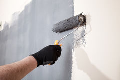 Renovation of interior. Man hand holds paint roller and painting wall with grey color. Royalty Free Stock Images