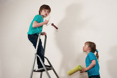 Renovation makes fun. Boy and girl  with paddle rollers making renovation in the house Royalty Free Stock Photos