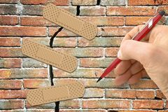 Renovation of an old brick wall - concept image with hand writing and adhesive bandage.  stock photo