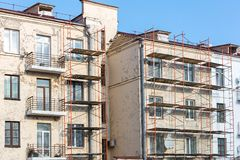 Renovation of old building facade. metal scaffolding near wall royalty free stock photo