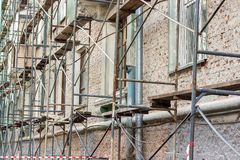 Renovation old building. Scaffolding during the repair of the facade of a multi-storey reential building Royalty Free Stock Image