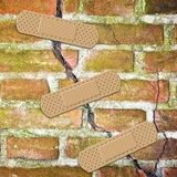 Renovation of an old cracked brick wall - concept image with bandaid patch.  royalty free stock photos