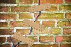 Renovation of an old cracked brick wall - concept image with bandaid patch.  stock images
