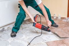 Renovation of old floor. Demolition of old tiles with jackhammer Royalty Free Stock Photo