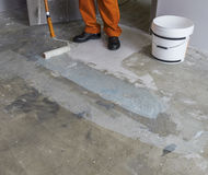Renovation of partment. Worker puts primer with roller on concre Royalty Free Stock Image