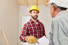 Renovation planning with craftsman and artisan. In cooperation royalty free stock images