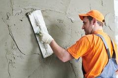 Renovation. Plasterer putting plaster on wall. stock photos