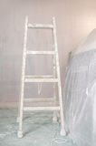 Renovation of a wall in empty room with ladder Royalty Free Stock Photo