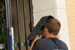 A welder placing a new iron door at the entrance of the apartment building with electric arc welding. Renovation works of the main door of an apartment building Stock Photo