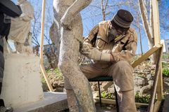 Renovator is engaged in the restoration of the statue royalty free stock photo