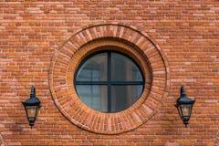 Renoverad vägg av en gammal textilfabrik med det runda fönstret och två lyktor royaltyfria bilder