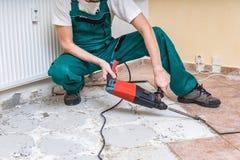 Renovering av det gamla golvet Rivning av gamla tegelplattor med tryckluftsborren royaltyfri foto