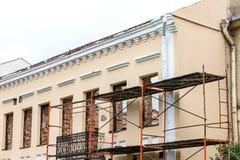 Renovering av gammal bostads- byggnad med materialet till byggnadsställning nära fac arkivbilder