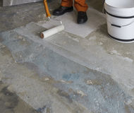 Renovering av huset Arbetaren sätter abc-bok med rullen på betong Royaltyfri Foto