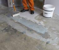 Renovering av partmenten Arbetaren sätter abc-bok med rullen på concre Royaltyfri Bild