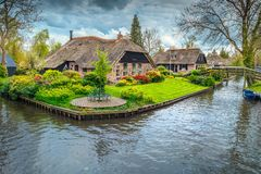 Dutch village with colorful ornamental garden and spring flowers, Giethoorn. Renowned old dutch village, traditional houses, decorated ornamental gardens with royalty free stock photo