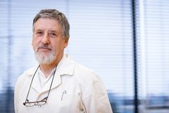 Renowned scientist/doctor. In a research center/hospital laboratory looking confident (color toned image; shallow DOF Stock Photo