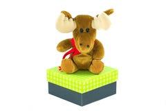 Renpuppe für Weihnachten über einer Geschenkbox lokalisiert auf weißem Ba lizenzfreies stockbild