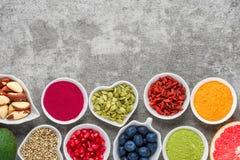 Rent ätaval för sund mat: frukt grönsak, frö, superfood, muttrar, bär på grå konkret bakgrund royaltyfri foto