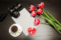 Rent ark av papper, rosa tulpan, en kamera och en råna av kaffe svart tabell Arkivbild