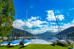 Rent-a-boat service in park at Zeller See lake. Zell Am See, Austria, Europe. Boats on shore and in water. Alps at background. Rent-a-boat service in park Royalty Free Stock Photos