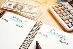 Rent or buy house pros and cons. Rent or buy house pros and cons on a notepad stock image