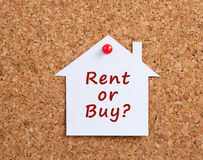 Rent or buy. White paper house on cork board with rent or buy text royalty free stock photography
