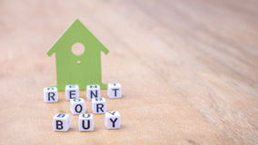 RENT OR BUY word of cube letters in front of green house symbols on wooden surface. Concept.  royalty free stock image