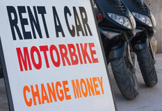 Rent a car sign with scooters Stock Photo