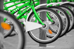 Rent a green bicycle. Urban scene with green bicycles for rent in a velo station Royalty Free Stock Images