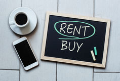 Rent not Buy blackboard concept. Choosing buying over renting. Rent not Buy blackboard concept. Choosing renting over buying with coffee and mobile phone Stock Image