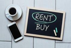 Rent not Buy blackboard concept. Choosing buying over renting. Rent not Buy blackboard concept. Choosing renting over buying with coffee and mobile phone stock image