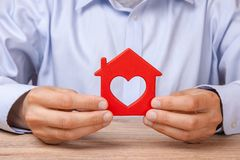Rent or purchase a house. Man is holding red house with heart royalty free stock photography