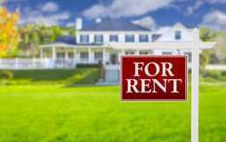 For Rent Real Estate Sign in Front of House. Red For Rent Real Estate Sign in Front of Beautiful House royalty free stock images