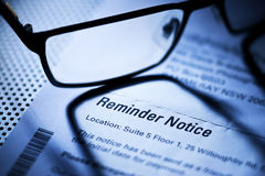 Rent Reminder Notice Account Bills. A reminder notice to pay a bill with reading glasses royalty free stock photography