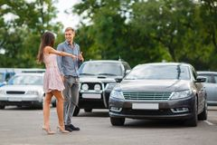 Young couple chooses used car in the street showroom. Royalty Free Stock Photo