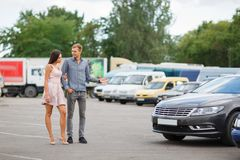 Young couple chooses used car in the street showroom. Stock Photo