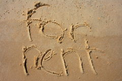 For Rent in sand. For Rent written in Sand royalty free stock images