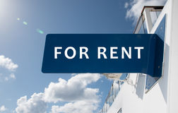 FOR RENT sign. Advertising concept: Rent text sign with blue and white colors. Sky background stock image