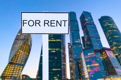 For Rent sign against blurred evening skyscrapers or office buildings background.  royalty free stock photo
