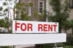 For rent sign with homes in background. Photo of for rent sign with homes in background royalty free stock photos