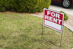 For rent sign with homes in background. Photo of for rent sign with grass copy space area royalty free stock photo
