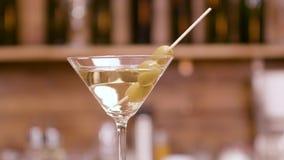 Rent slut upp parallaxskott av ett martini exponeringsglas som garneras med oliv arkivfilmer