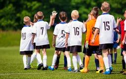 Rent spelregler i ungdomfotboll Lyckliga fotbollsspelare som ger höjdpunkt fem på fältet Fotbollspelare höga fem efter lek Arkivfoton