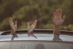 Rent trans. Hållbar eller grön transport Händer som gör en gest i öppen billucka Resa med bilen enjoying arkivbilder