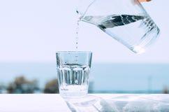 Rent vatten från en tillbringare hälls in i en exponeringsglasdryckeskärl Exponeringsglas med vatten på bakgrunden av havet royaltyfri foto