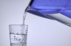 Rent vatten från filtret som häller i ett exponeringsglas Arkivbild